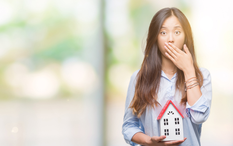 Young asian woman real state agent holding house isolated background cover mouth with hand shocked with shame for mistake, expression of fear, scared in silence, secret concept