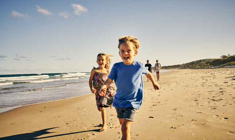Shot of two adorable little children running at the beach with their parents in the background